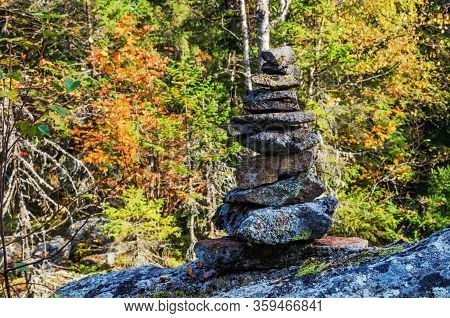 Pyramid Of Stones On The Mountainside Against The Background Of An Autumn Forest In The Sunny Day