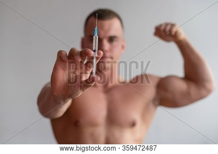 Attractive Male Bodybuilder With A Naked Torso Holds A Dope Syringe. The Athlete Puts Himself An Inj