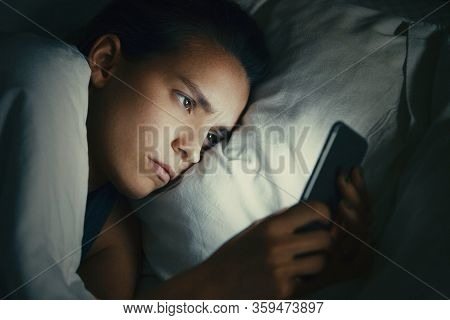 Young Beautiful Womanl In Bed Using Mobile Phone Late At Night At Dark Bedroom, Internet Addiction C