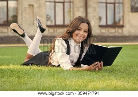After-school Lesson. Small Girl Read Lesson Book On Green Grass. Happy Little Child Relax With Book