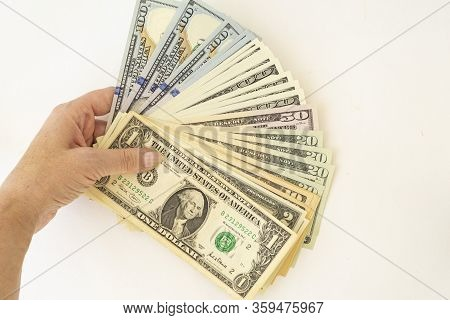 A Female Hand Holds Several Hundred Dollar Bills Spread Out In A Fan On A White Background. There Is