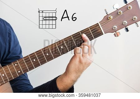 Learn Guitar - Man In A Dark Blue Shirt Playing Guitar Chords Displayed On Whiteboard, Chord A6