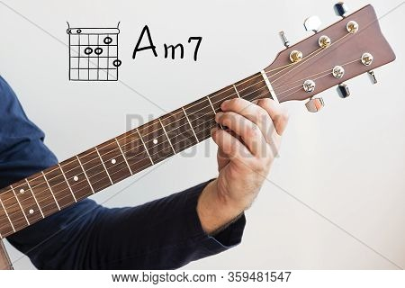 Learn Guitar - Man In A Dark Blue Shirt Playing Guitar Chords Displayed On Whiteboard, Chord A Minor