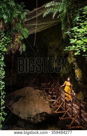 Gorgeous Woman In Yellow Sundress Looking At Caves With River Creek