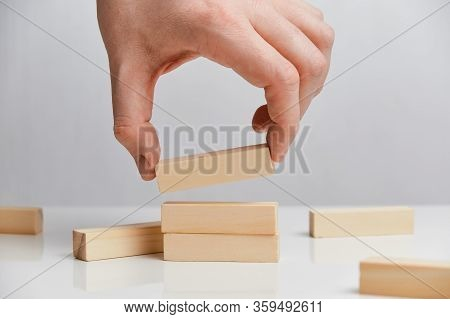Concept Of Rebuilding A Business After Bankruptcy. Hand Holds Wooden Blocks On A White Background. C