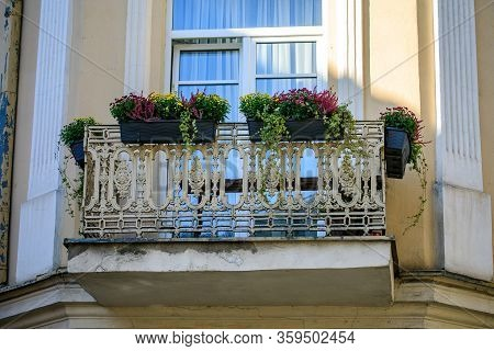 White Ornate Wrought Iron Balcony Decorated With Flowers In Vilnius Old Town