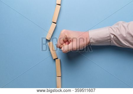 The Concept Of Breaking Stereotypes. Hand Holds Wooden Blocks On A Blue Background. Close Up.