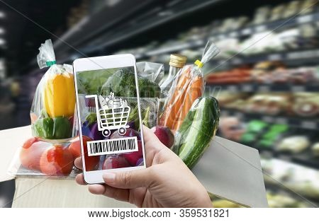 Online Order Grocery Shopping On Touch Screen Concept. Woman Hand Holding Smart Phone With Checks Th