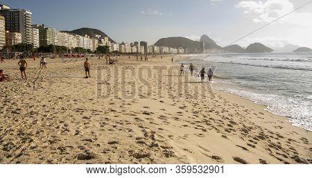 Rio De Janeiro, Brasil- March 05, 2020: Citizens Swim And Sunbathe On The Beach Of Copacabana