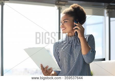 Attractive African American Business Woman Talking With Collegues On The Mobile Phone.