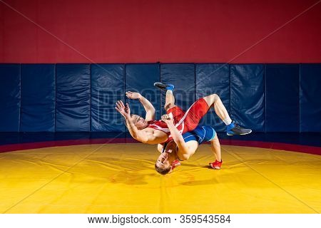Two Greco-roman  Wrestlers In Red And Blue Uniform Wrestling  On A Yellow Wrestling Carpet In The Gy