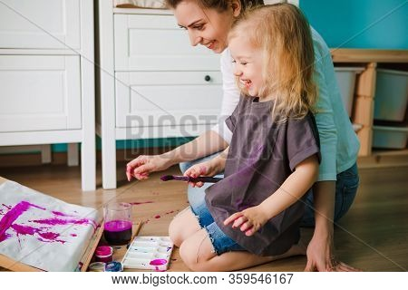 Mom And Daughter Draw With Pencils And Paints While Sitting On The Floor In The Games Room.