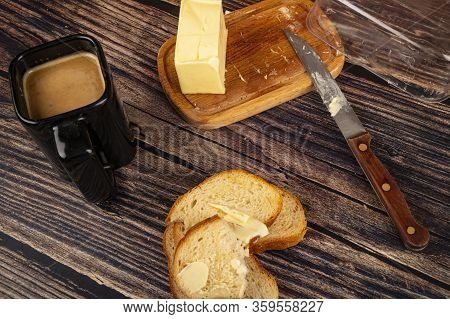 Fresh Wheat Toast With Butter, A Black Ceramic Mug With Coffee And Milk, And A Wooden Butter Dish Wi