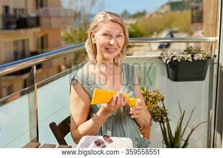 Woman On A Hotel Terrace By The Sea.woman Applying Sun Cream On Tanned Shoulder. Sun Protection. Ski