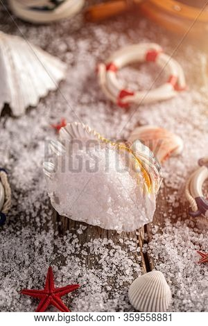 Pile Of Sea Salt In Shell On Wooden Background