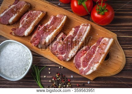 Raw Slices Of Pork Bacon On A Cutting Board, On A Rural Wooden Tabletop. Pork Belly With Vegetables.