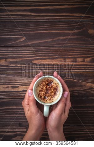 Female Hands Holding A Cup Of Coffee With Foam Over A Wooden Table, Top View. Latte Or Cappuccino Wi