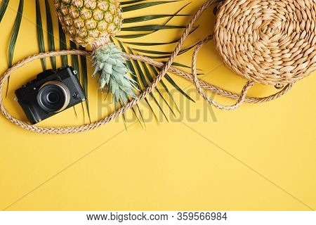Flat Lay Traveler Accessories On Yellow Background. Frame Border Made Of Palm Leaf, Rattan Straw Bag
