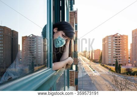 Bored Woman With Ffp2 Face Mask Peeks Out The Window During Quarantine Over Covid-19 Crisis. Stay At