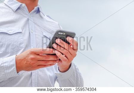 Close Up Of Young Businessman Using Mobile Phone App Texting Outside Of Office In Urban City With Sk