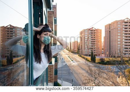 Desperate Woman With Ffp2 Face Mask Peeks Out The Window During Quarantine Over Covid-19 Crisis. Sta