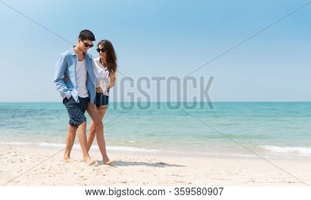 Portrait Of Romantic Young Couple In Casual Wear Sun Glasses Walking At The Beach With Blue Sky. Hap