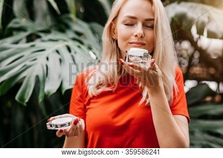 Good Looking Caucasian Young Woman With Healthy Perfect Skin Holding Jar Of Face Cream Or Sunblock,