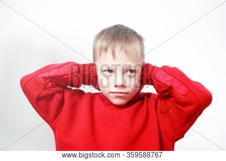 Six-years Old Boy In Red Hoodie Closing Ears With His Hands On Grey Background. Autism Concept. Chil