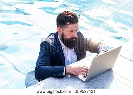 Freelancer Working On Vacation Next To The Swimming Pool. Businessman Using A Computer In Pool. Funn