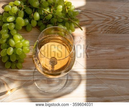 White Wine Glass On Ripe Green Grapes Background In Sunny Day