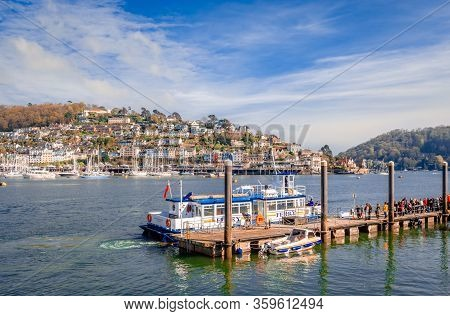 Dartmouth / UK - April 21 2014: The passengers are ready to embark on the ferry, at the North Embankment terminal. Kingswear, a village located on the east bank of river Dart, is in the background.
