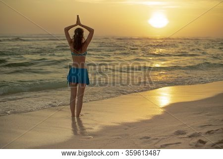 Yoga Pose. Silhouette Of Woman Standing On The Beach, Practicing Yoga. Young Woman Raising Arms With