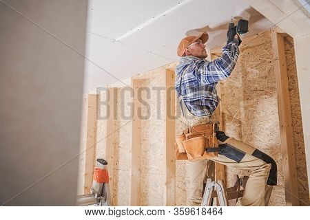 Caucasian Construction Contractor Worker Attaching Drywall To A House Ceiling. Construction Industry