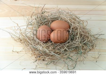 Fresh Brown Chicken Eggs In Hay Nest On Blue Wooden Background. Concept Of Organic Eggs, Free Space