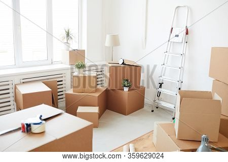 Wide Angle Background Of Stacked Cardboard Boxes In Empty White Room, Moving, Relocation And House D