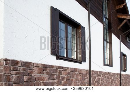 Facade Of A Cottage In The Style Of A Chalet. Chalet House. Windows In A Large Chalet Cottage.