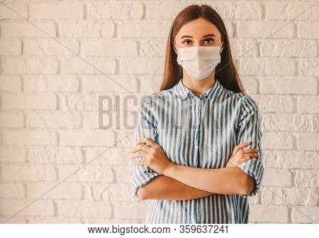 Young Girl Female Doctor In Protective Mask On Face Keeping Arms Crossed In Hospital. Confident Sick