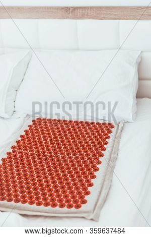 Acupuncture Mat In Bed. Wellness, Reflexology And Self Care Treatment At Home Concept. Alternative T