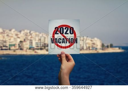 Hand Holds A Text Message On 2020 Cancelled Summer Vacation Over An Exotic Seashore Background. Holi