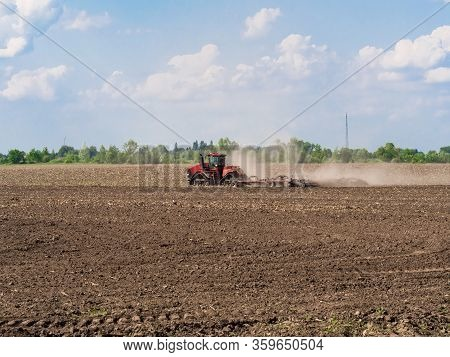 Farmer Cultivating Arable Land Before Seeding. Tractor Working On The Farm, A Modern Agricultural Tr