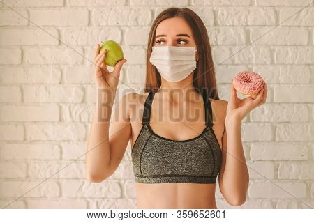 Young Fitness Girl In Medical Face Mask Hold Apple And Donut In Hands At Home. Fit Woman Sports Inst