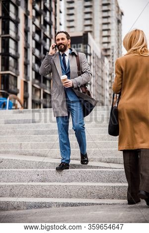 Man With A Phone Descending The Stairs