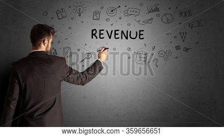 businessman drawing a creative idea sketch with REVENUE inscription, business strategy concept