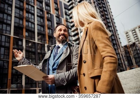 Realtor Looking At A Pleased Female Client