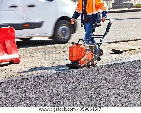 A Road Worker Compacts Asphalt On The Carriageway With A Gasoline Vibratory Compactor.