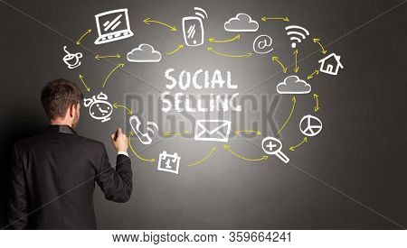 businessman drawing social media icons with SOCIAL SELLING inscription, new media concept
