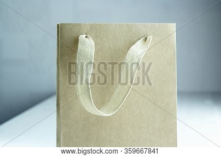Disposable Small Craft Paper Bag For Takeaway On White Table In The Interior. Packaging Template Moc