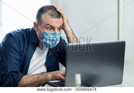Coronavirus News. Shocked Man Using Laptop Reading Shocking News Wearing Protective Medical Mask Sit
