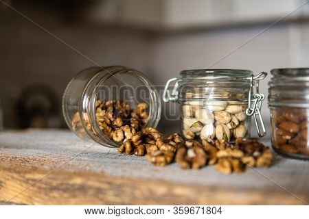 Walnut Scattered On The White Vintage Table From A Jar. Walnut Is A Healthy Vegetarian Protein Nutri