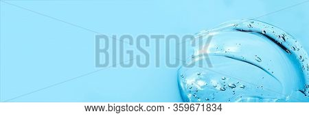 Hyaluronic Acid Cosmetic Gel. Gel Texture With Bubbles On A Blue Background. Transparent Smear Of Ge